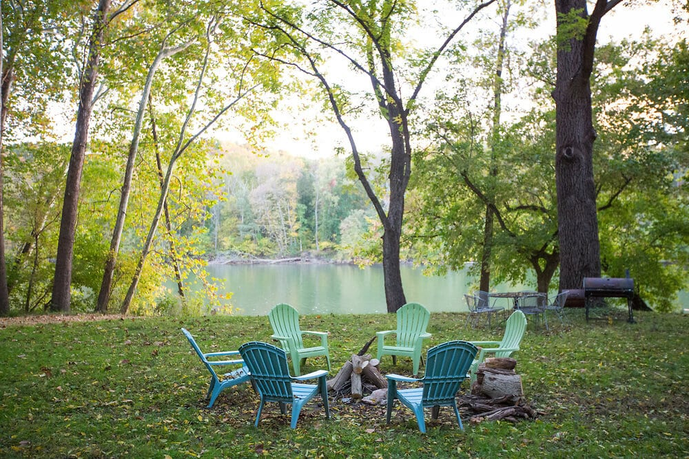 lawn chairs around a fire pit near a river